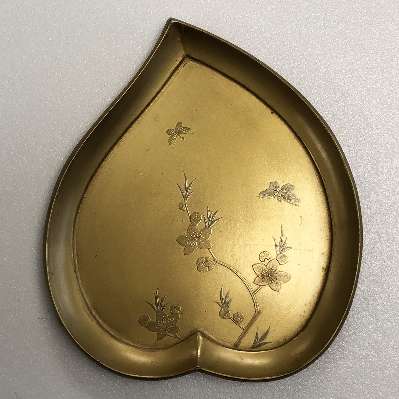 A peach-shaped tray with a design of delicate branches and butterflies in relief.