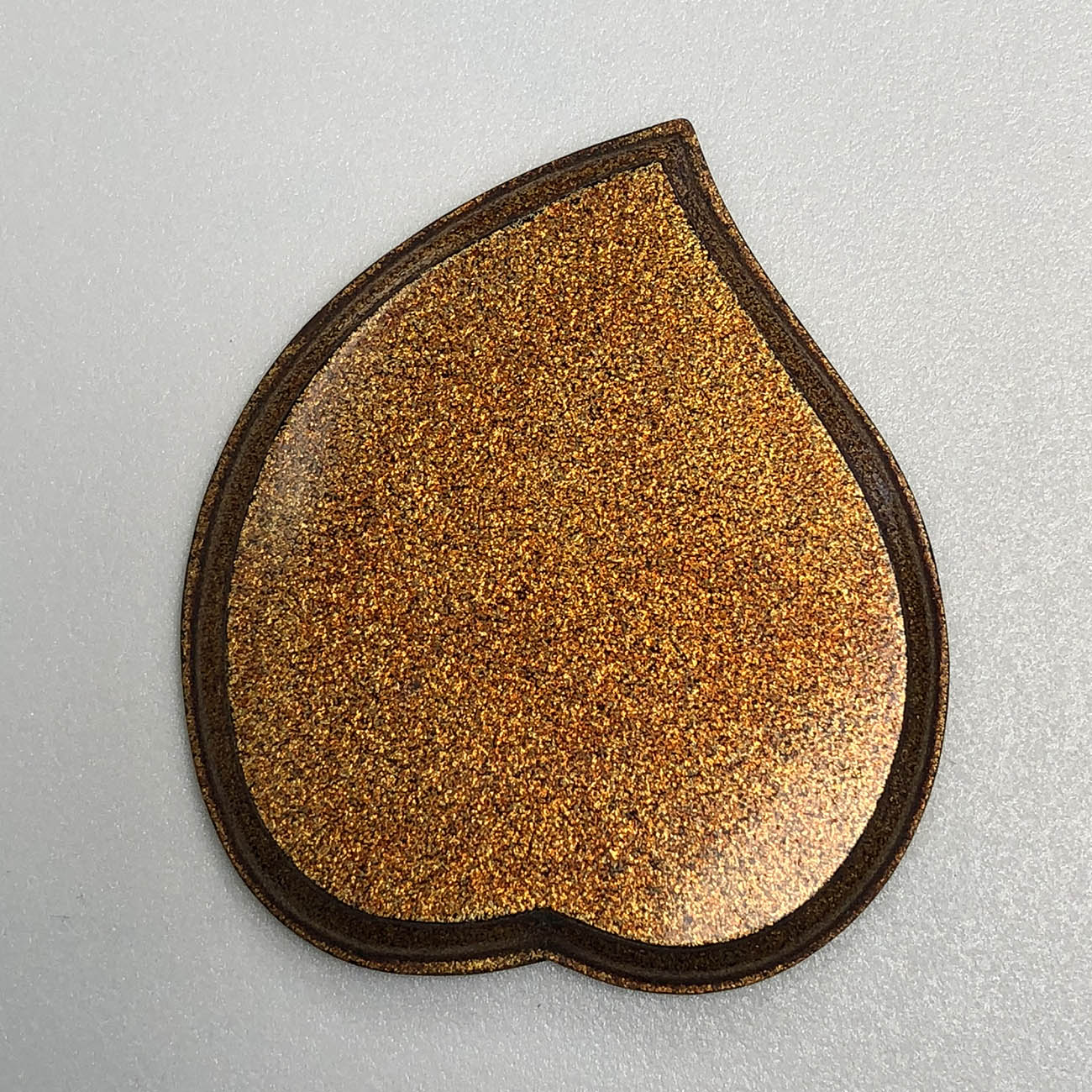 Underside of a peach shaped tray that is smooth and covered in what looks like a dense layer of gold and copper glitter.
