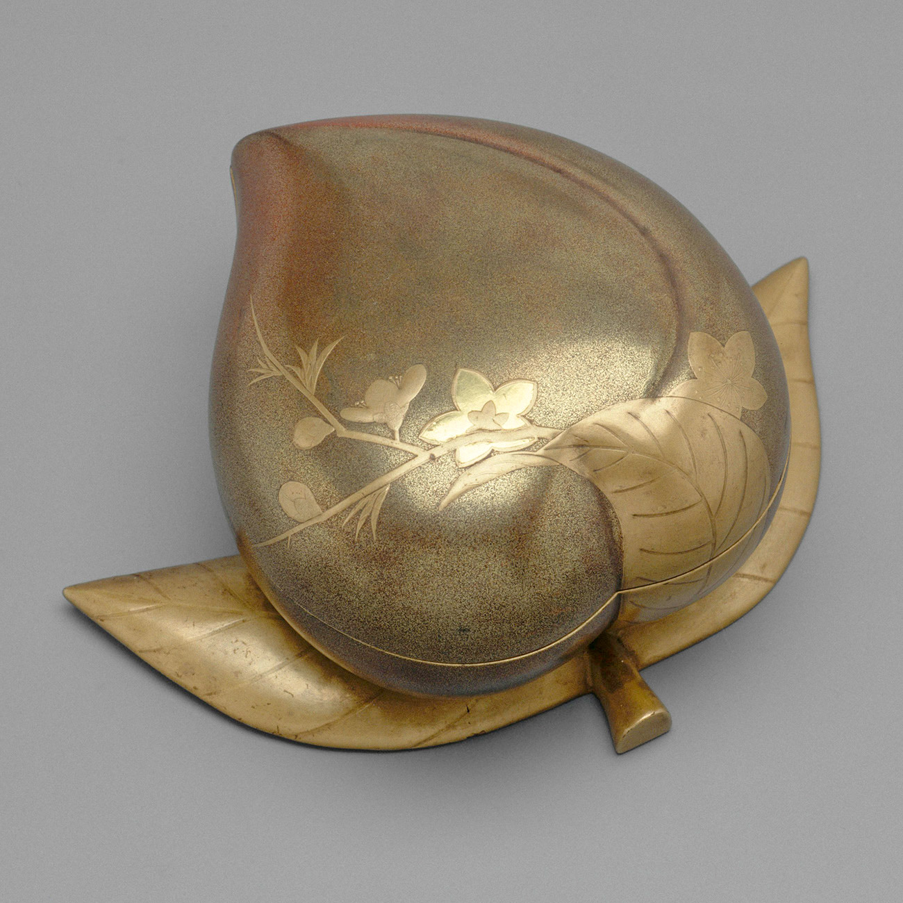 Another view of the top of the peach-shaped box showing two leaves spreading outward as a base and one more in relief on the top.