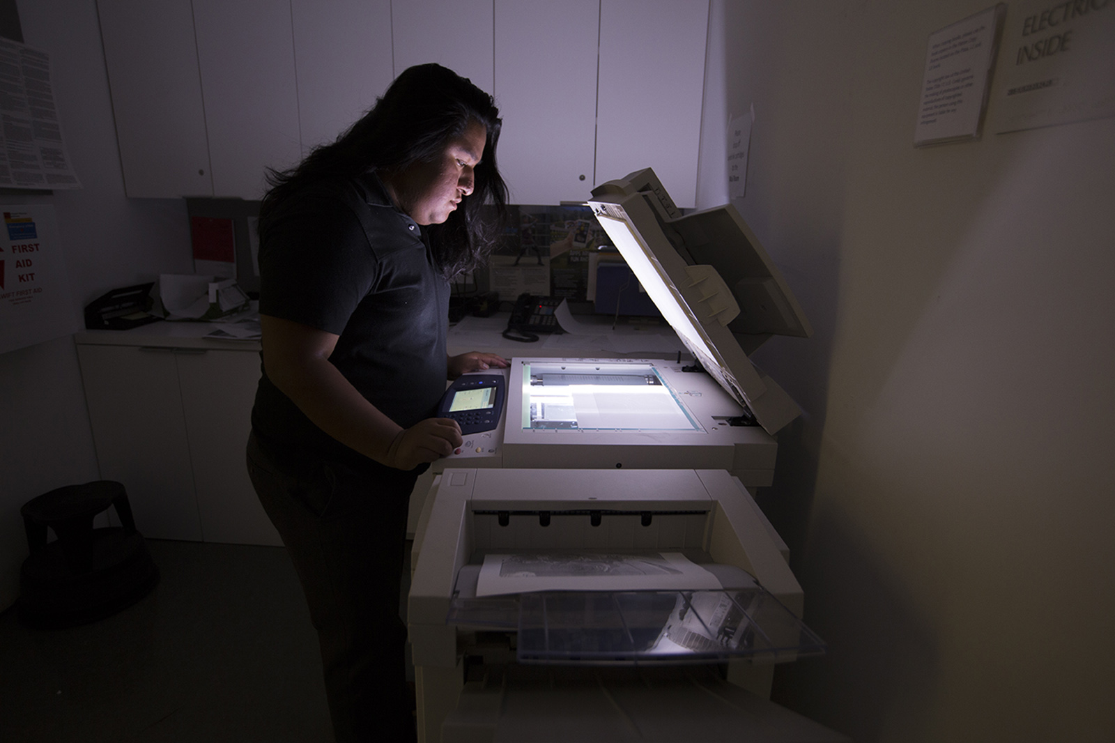 A young man with long hair uses a copy machine with the cover open, illuminating him in the dark room.