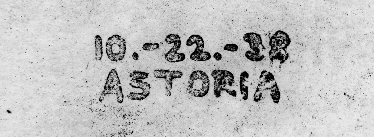 "A spattered black-and-white xerographic copy of a handwritten message reading ""10.-22.-38 ASTORIA."""