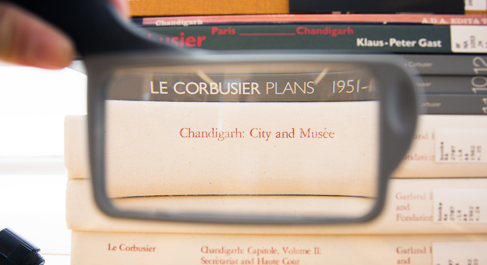 A magnifying glass focused on a book about Le Corbusier