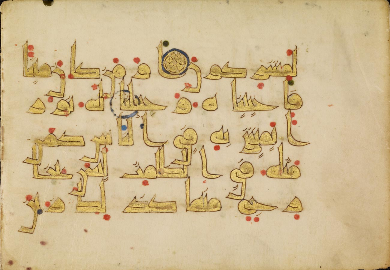An illuminated manuscript with large arabic letters in gold leaf with red dots and several blue circles and dots.