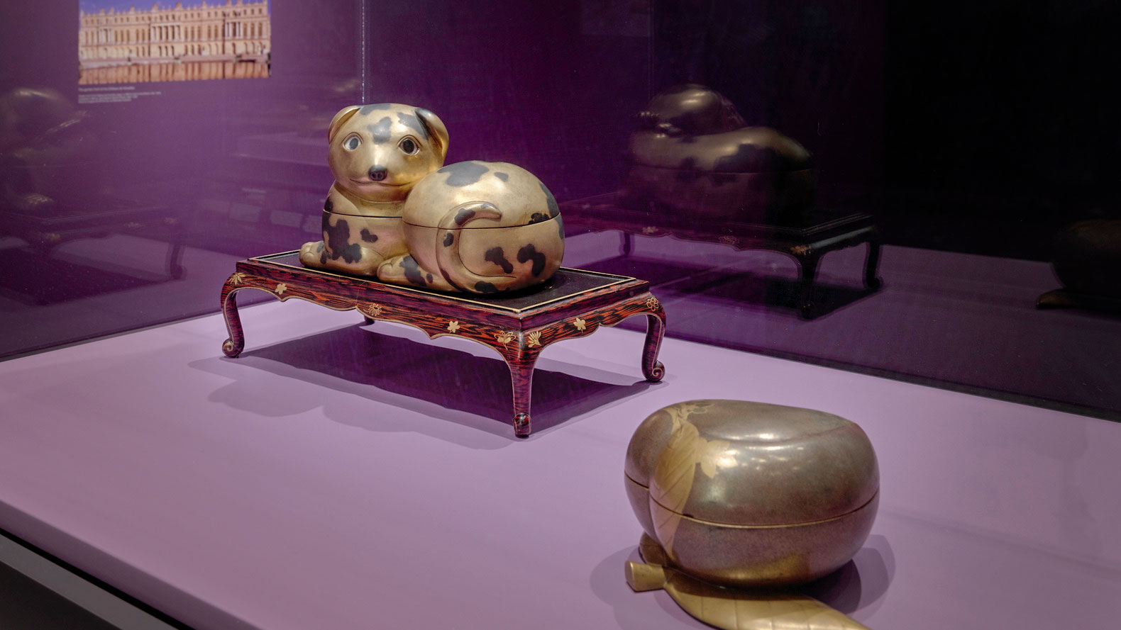 Two gold colored vessels appear in a museum case: a spotted dog and a pear with a leaf.