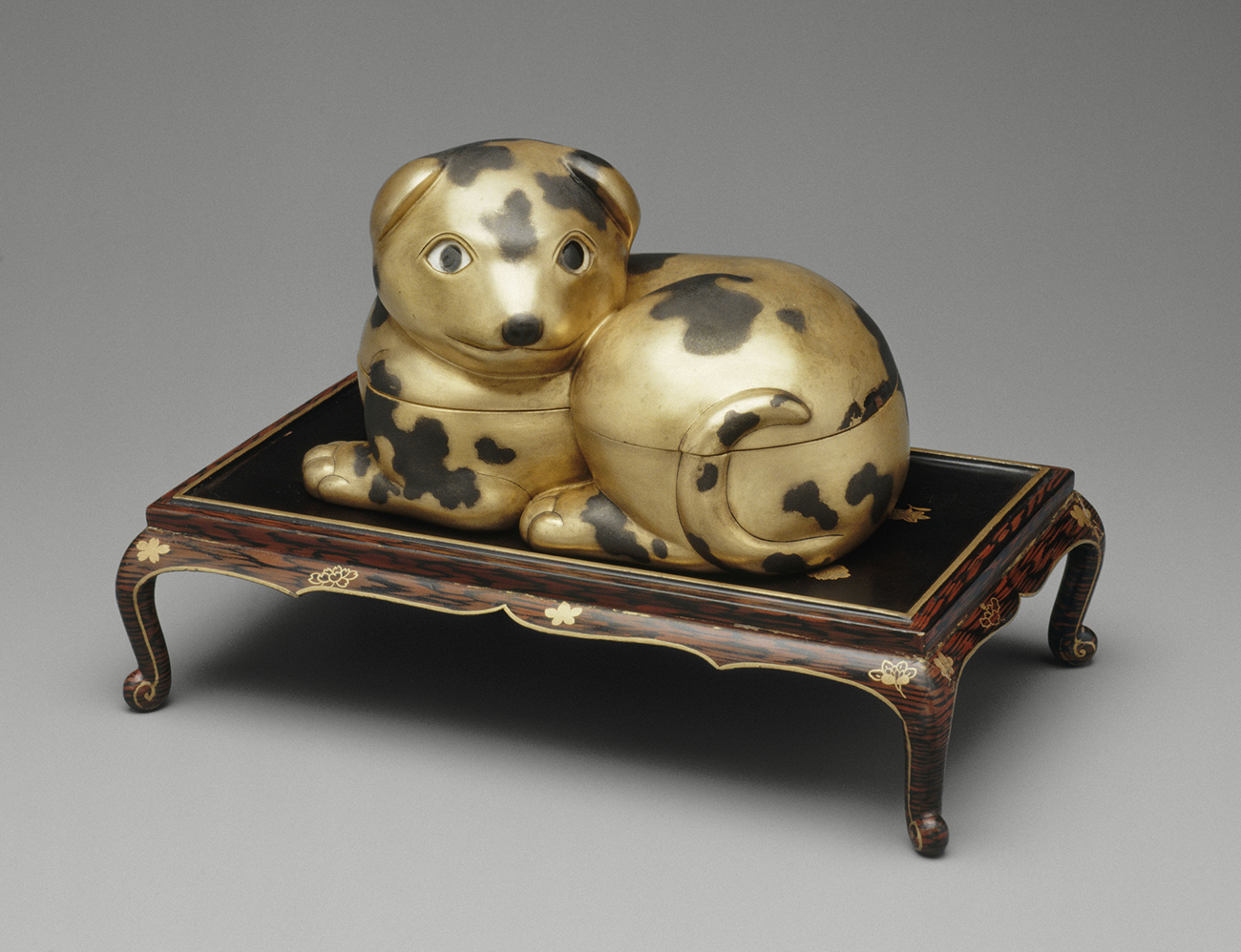 A gold colored box with a seam showing a top and bottom in the shape of a happy looking dog with spots on top of a small decorated wooden stand.