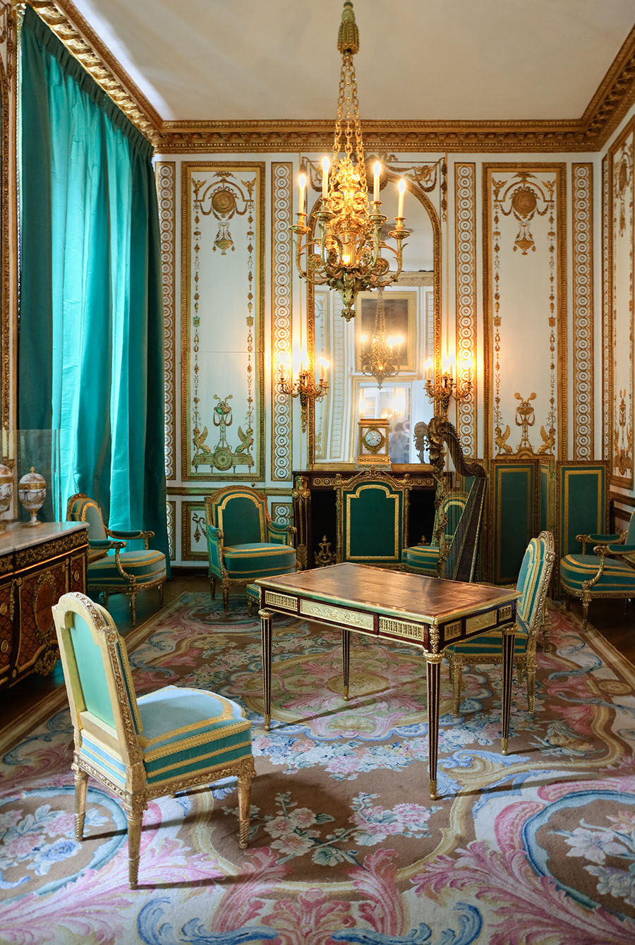 A highly ornate room with lush complex gold patterns and 18th century furniture.