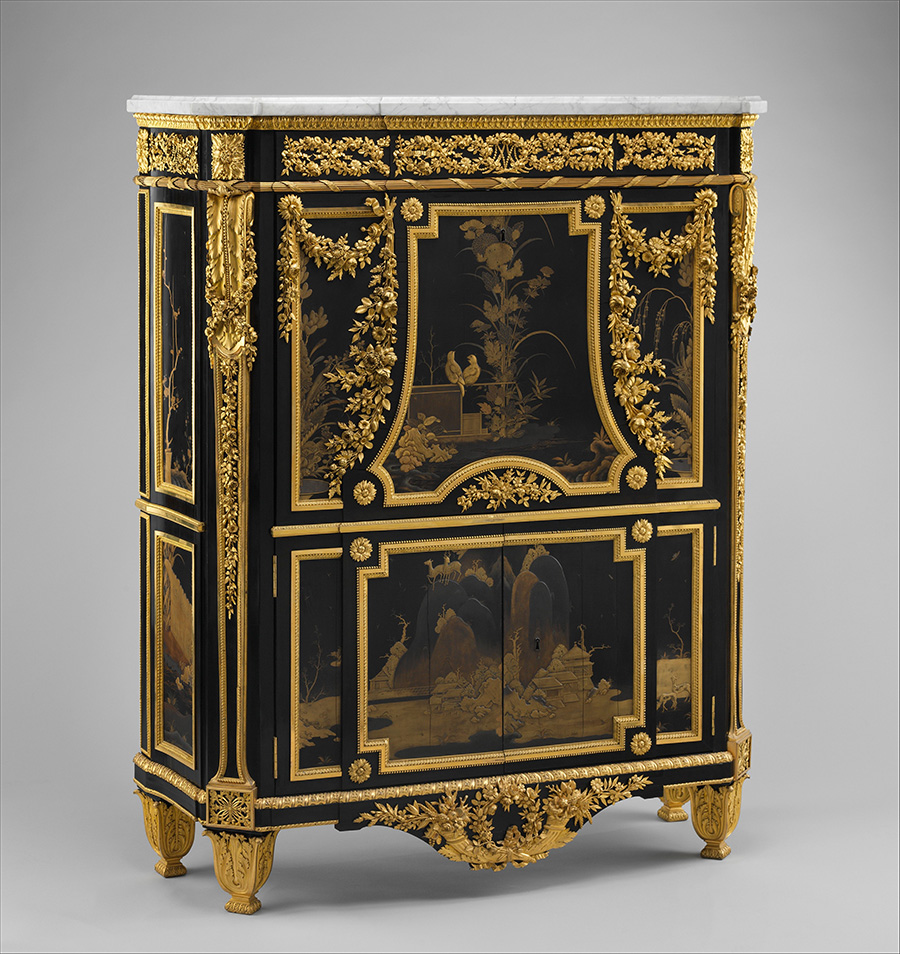A black cabinet with gold decorations. A Japanese landscape appears on the bottom cabinet doors and to top cut-away reveals a scene centered on two gold birds that seem to be conversing.
