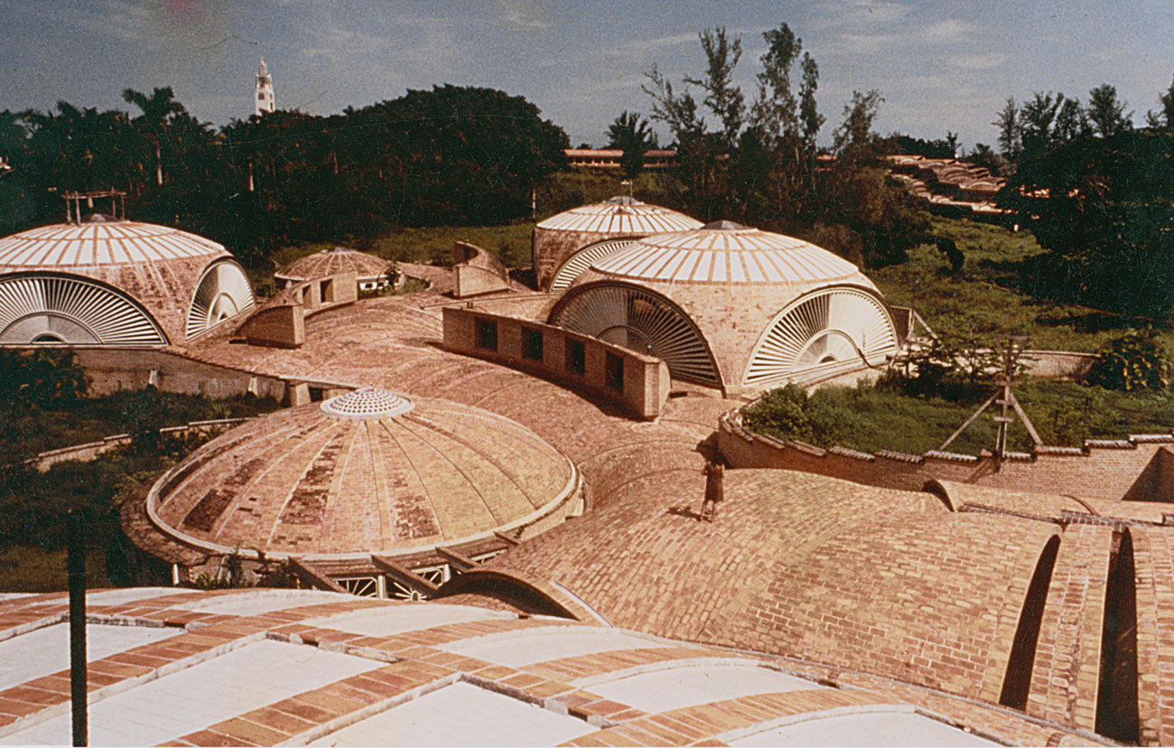 A view looking down upon a campus of brick domed structures nested in trees and greenery.