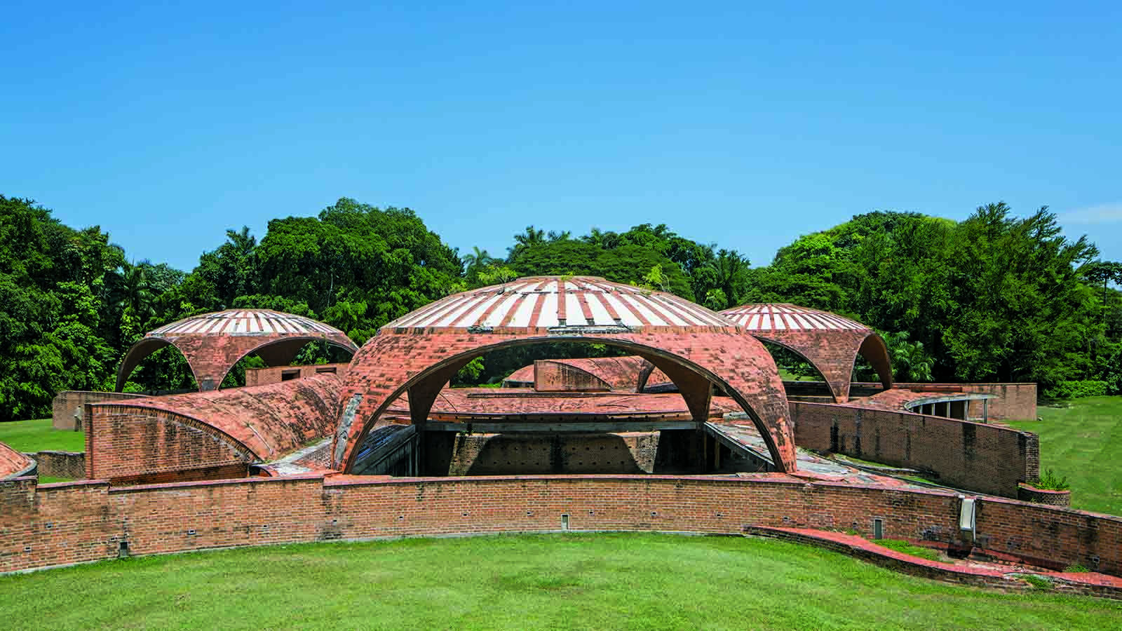 A group of brick structures formed of domes and arches with large open air spaces, surrounded by grass and trees.