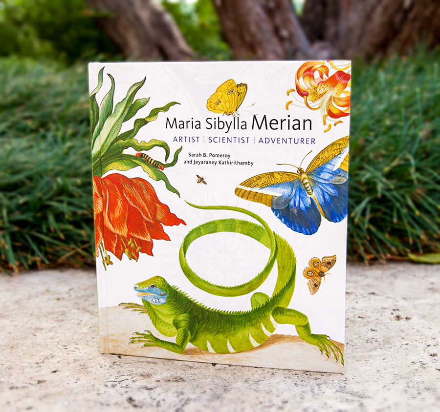 A book with bright animal, insect and plant illustrations and the title , Maria Sibylla Merian: Artist, Scientist, Adventurer, sits upright outside on a marble tile with plants behind it.