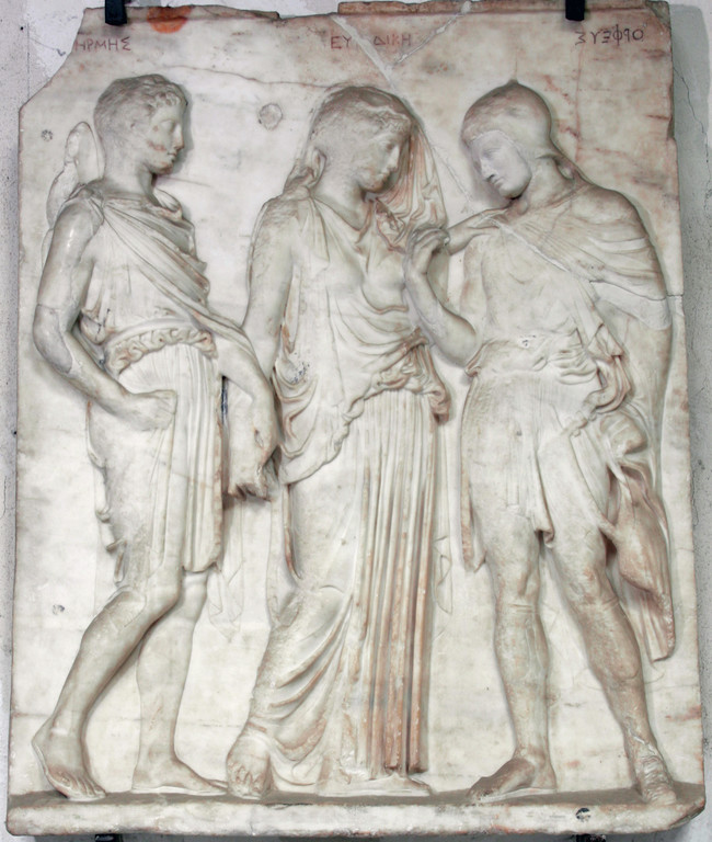 Photograph of a marble relief with three figures carved in three-quarters view.