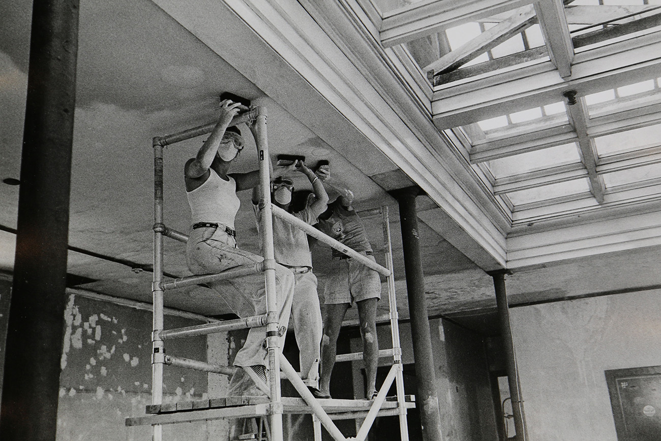 Three women wearing safety goggles and dust masks as they stand on scaffolding to sand the ceiling in the Woman's Building.