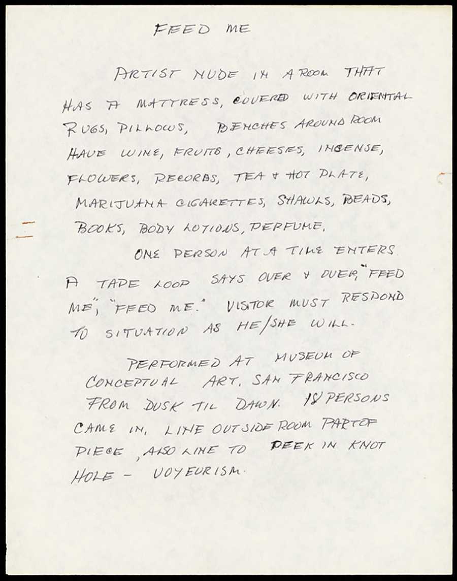 """Feed Me"" is handwritten in black ink at the top of a sheet of paper that reads: ""Artist nude in a room that has a mattress, covered with oriental rugs, pillows, benches around the room have wine, fruits, cheeses, incense, flowers, records, tea & hot plate, marijuana cigarettes, shawls, beads, books, body lotions, perfume. One person at a time enters A tape loop says over & over, 'Feed me', 'Feed me.' Visitor must respond to situation as he/she will. Performed at Museum of Conceptual Art, San Francisco From dusk till dawn. 18 persons came in, line outside room part of piece, also line to peek in knot hole – voyeurism"