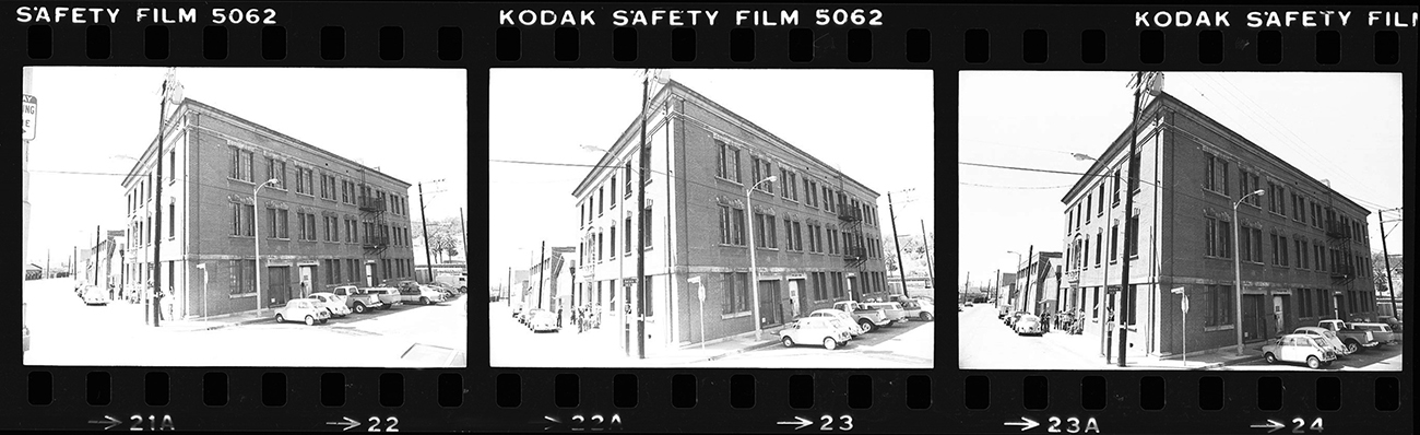 A strip of film shows three black-and-white photographs of the three-story, brick Woman's Building from a corner, each getting slightly closer in vantage point.