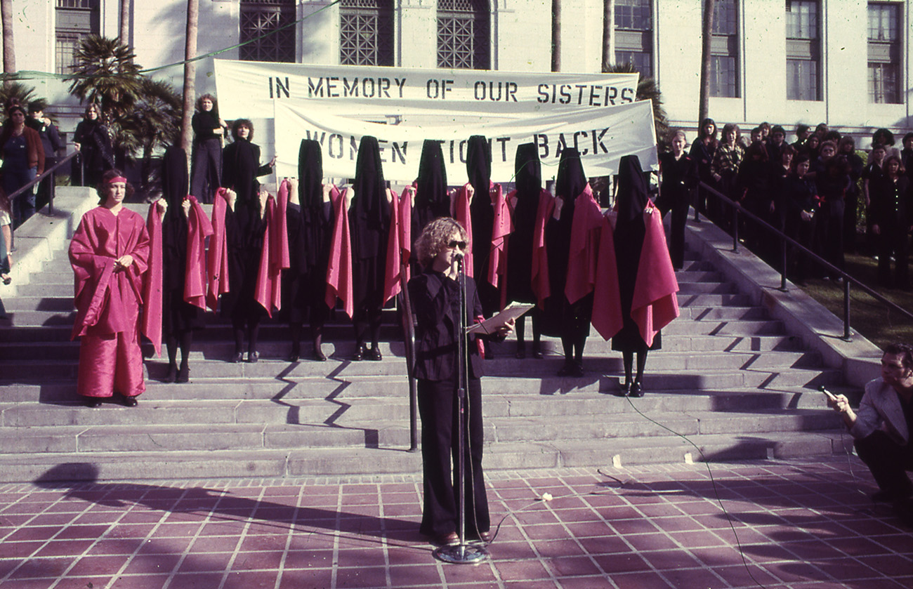 "On steps outside Los Angeles City Hall, a woman in a black suite talks into a microphone while several women in black and red behind her stand near and in front of banners that read ""In Memory of our Sisters"" and ""Women Fight Back."""