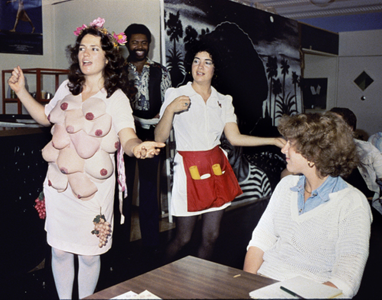 A woman wearing a dress covered in fake breasts and grapes and a woman wearing a white waitress outfit with a red apron gesture and perhaps sing to onlookers standing and sitting at tables.