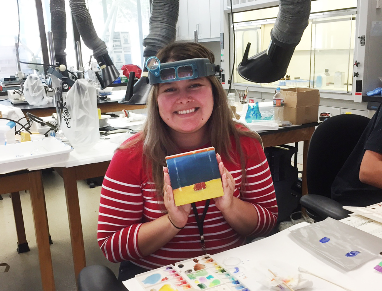 A female holds a tile towards the camera. She is wearing conservation goggles inside of a lab.