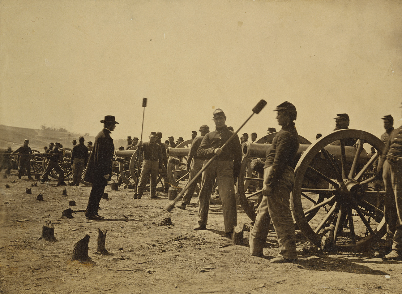 A historical photograph of soldiers in uniform preparing for a battle. A group of 30 or so solders stand next to canons, ready to light them.