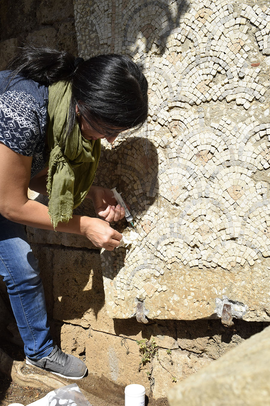 A woman uses a syringe to inject material into a mosaic with a scallop pattern that hangs on a wall.