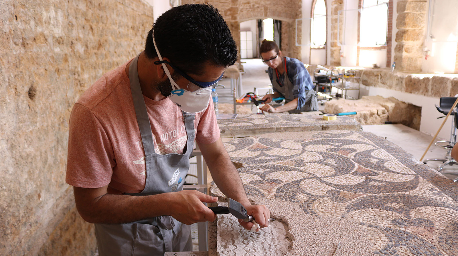 A man wearing a dust mask and safety goggles uses a hammer and chisel at an angle to chip away mortar that had filled a gap in a mosaic with a black and red decorative pattern against a white background.