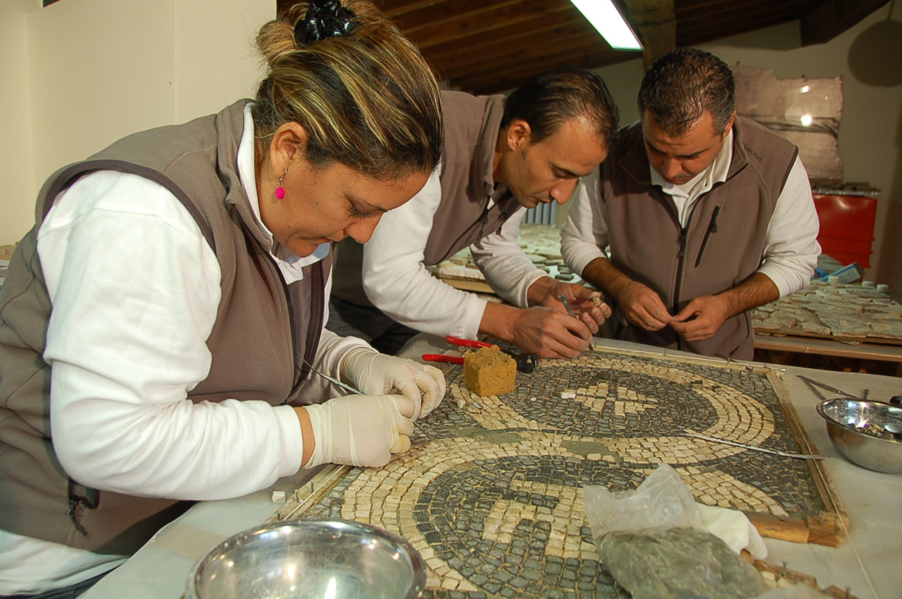 Three restorers in brown vests use small tools to clean a section of the black and white mosaic from the Quadraro Villa.