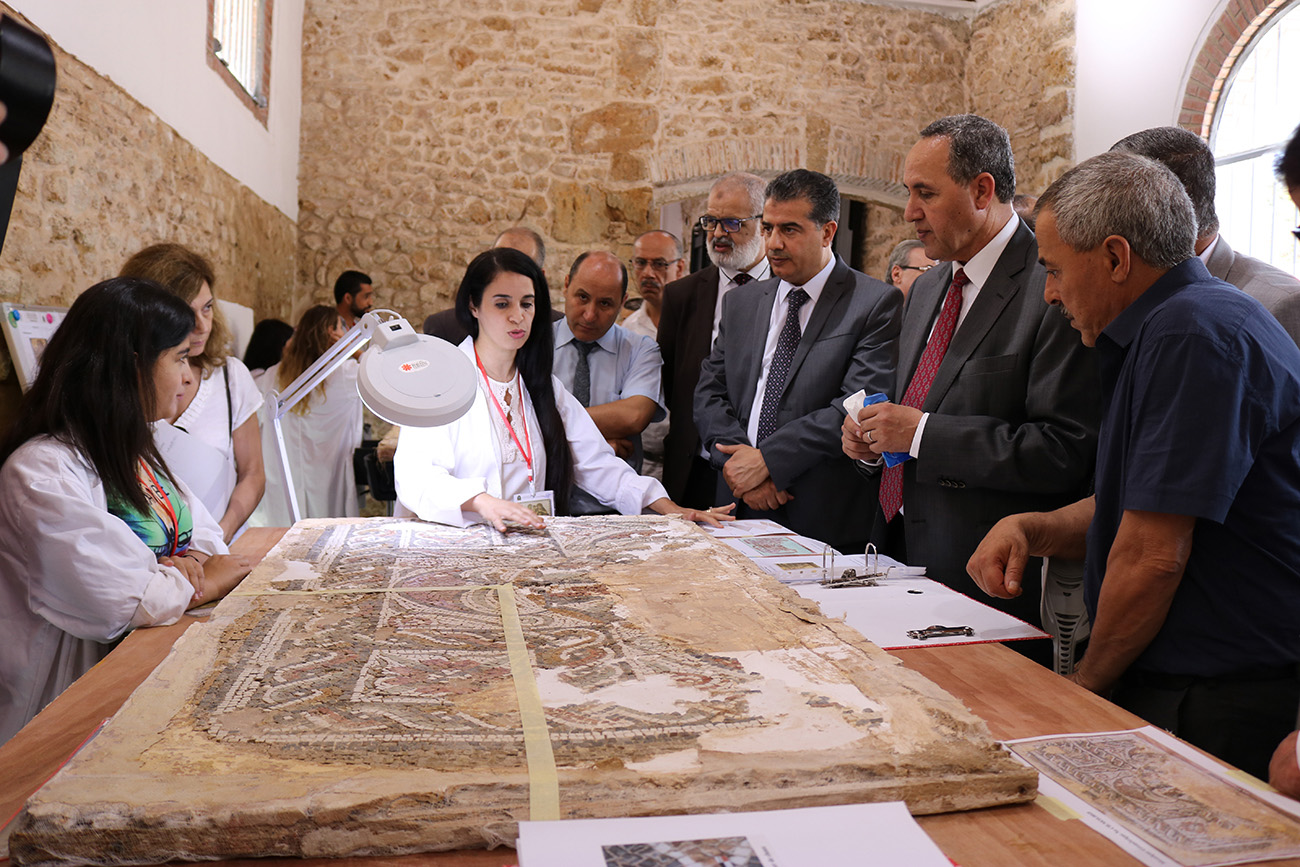 A woman in a lab coat gesture at a mosaic while talking to several men in suits standing around the table on which the mosaic sits.