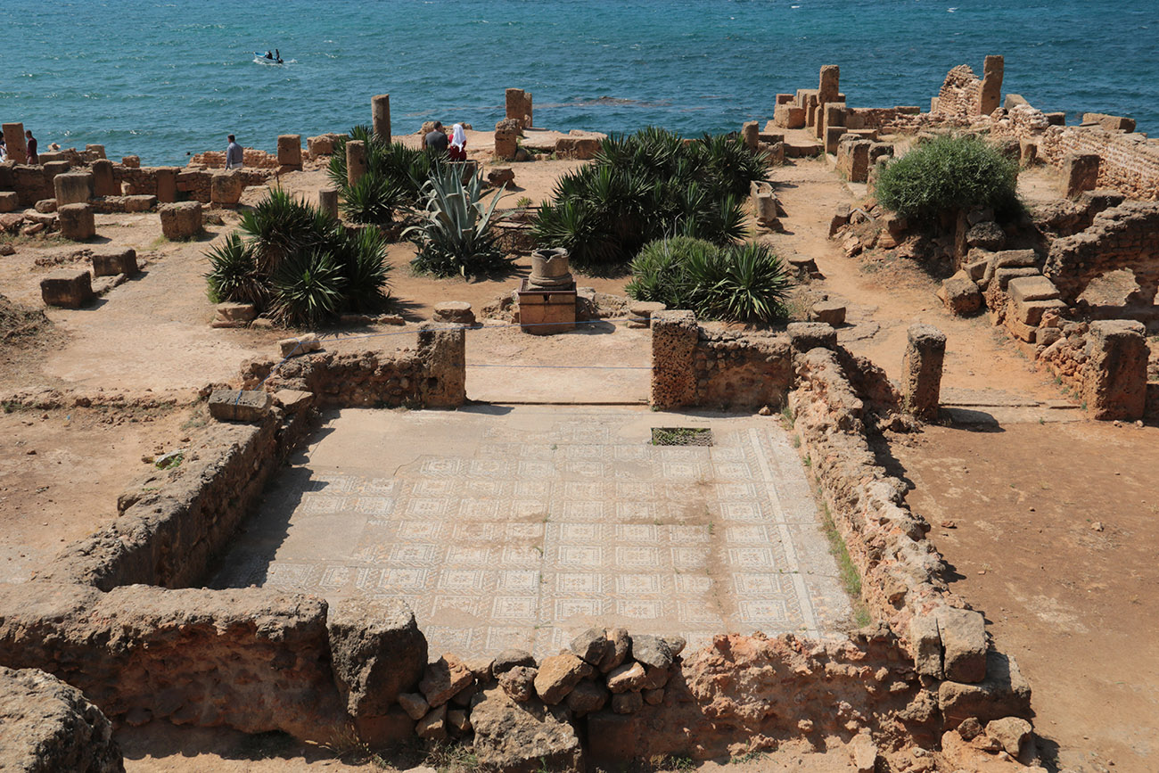 Ruins of a square building near a sea expose a mosaic floor.