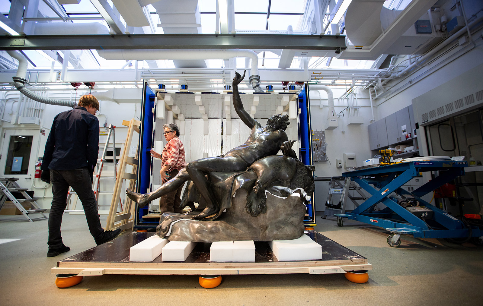 A man and a woman standing near a large bronze of a reclining male figure, half removed from its shipping crate