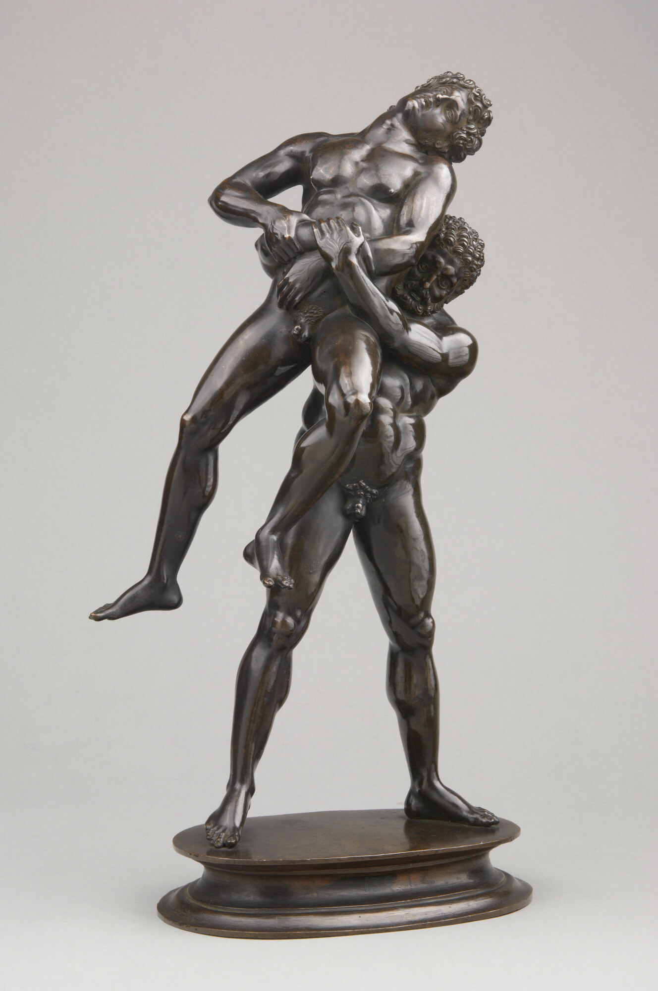 Two nude men wrestling, one holding the other aloft.