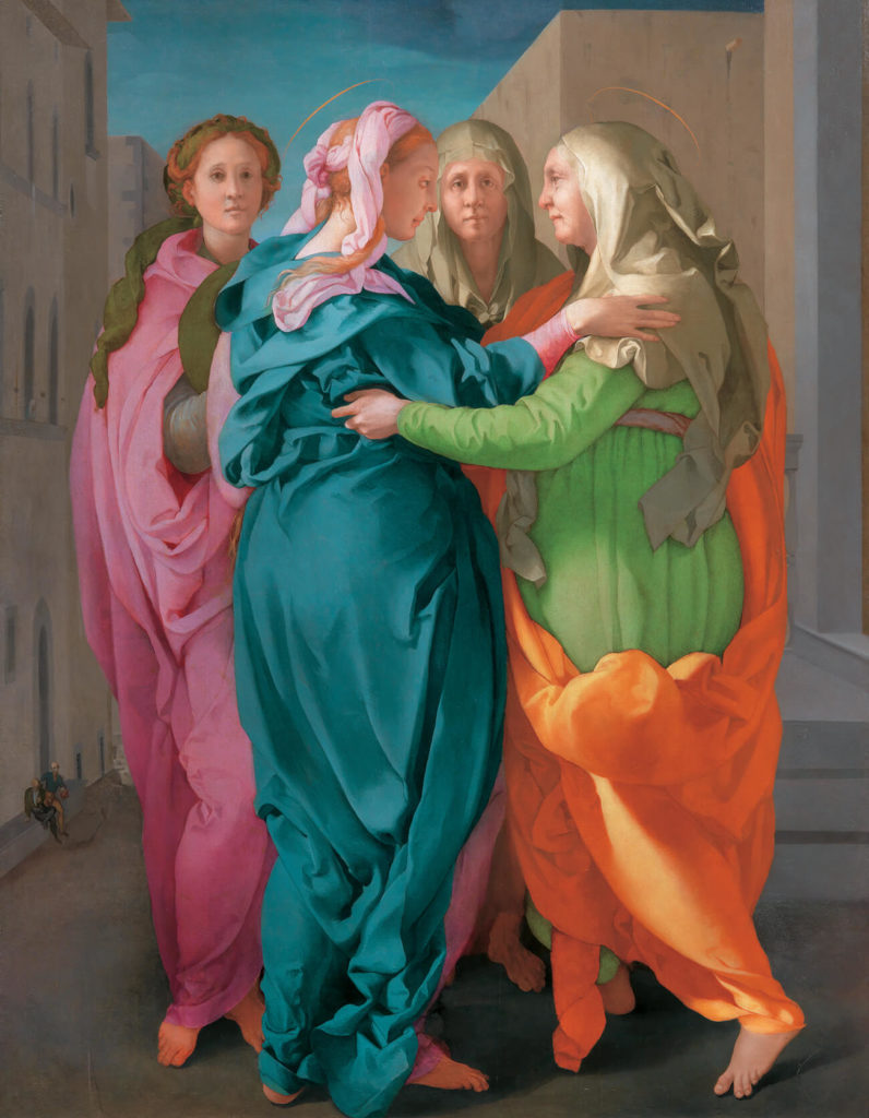 Four women in brightly colored togas greet each other on a street.