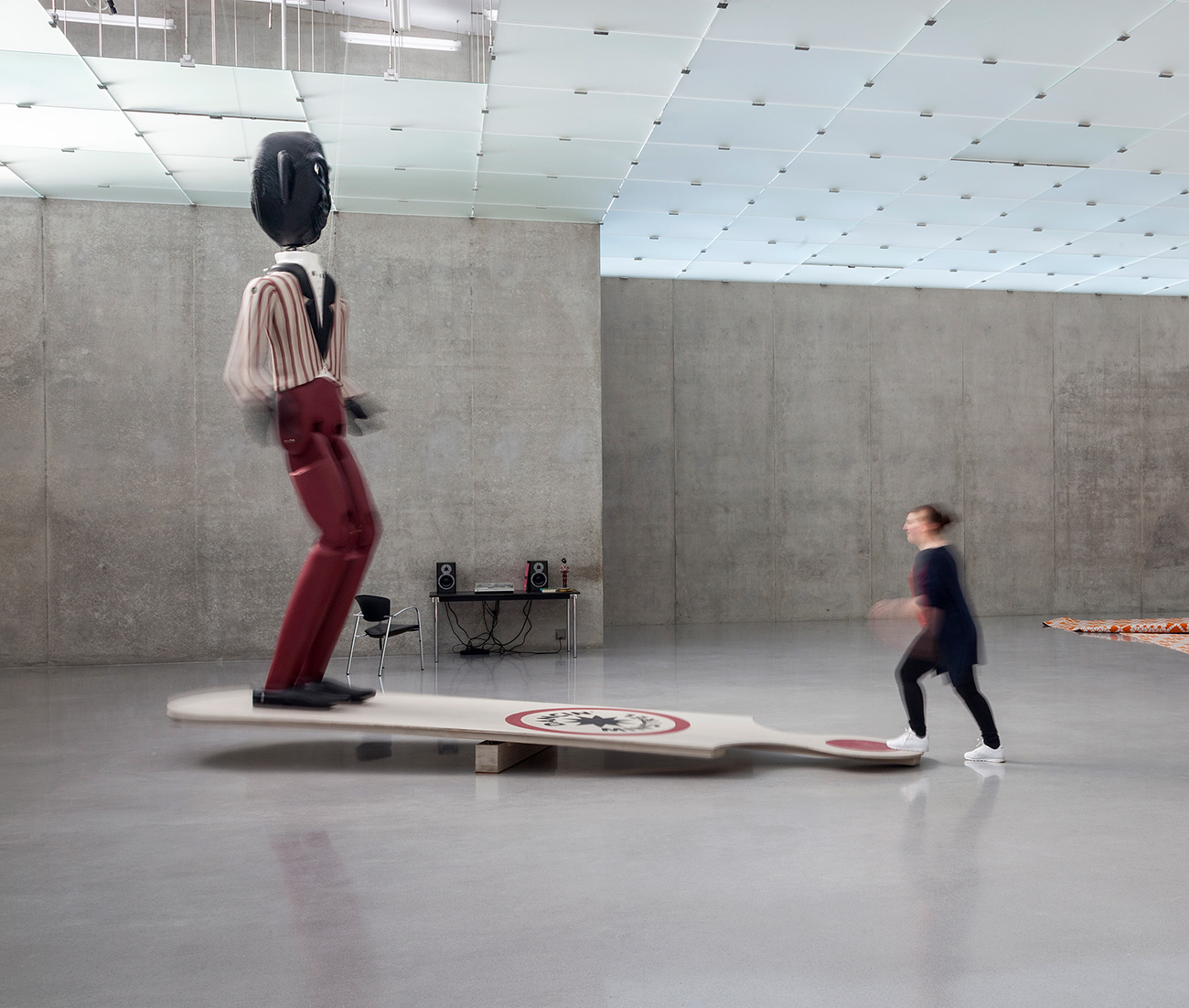 In a large room with concrete walls, a woman steps on one end of a large paddle board. On the other hand stands a large black-face minstrel statue that is approximately two and a half times the height of an average person.