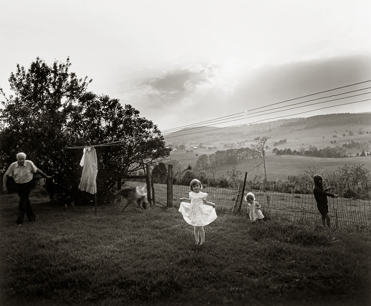 Black and white photo of a girl in a white dress in a yard, with two children playing behind her and an older man to the left.