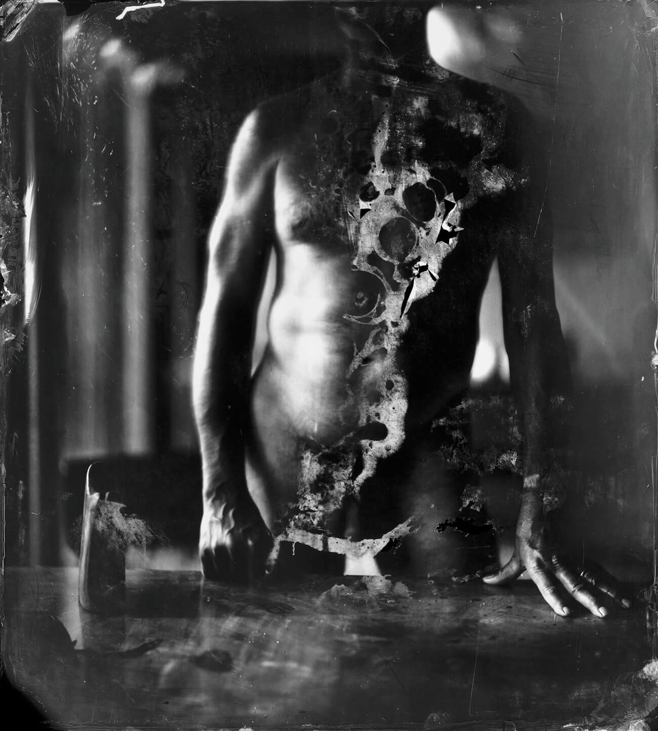 Black and white image of a nude man standing before a table.
