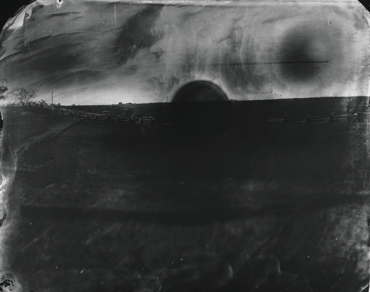 Black and white photo of the horizon with a dark semicircle.