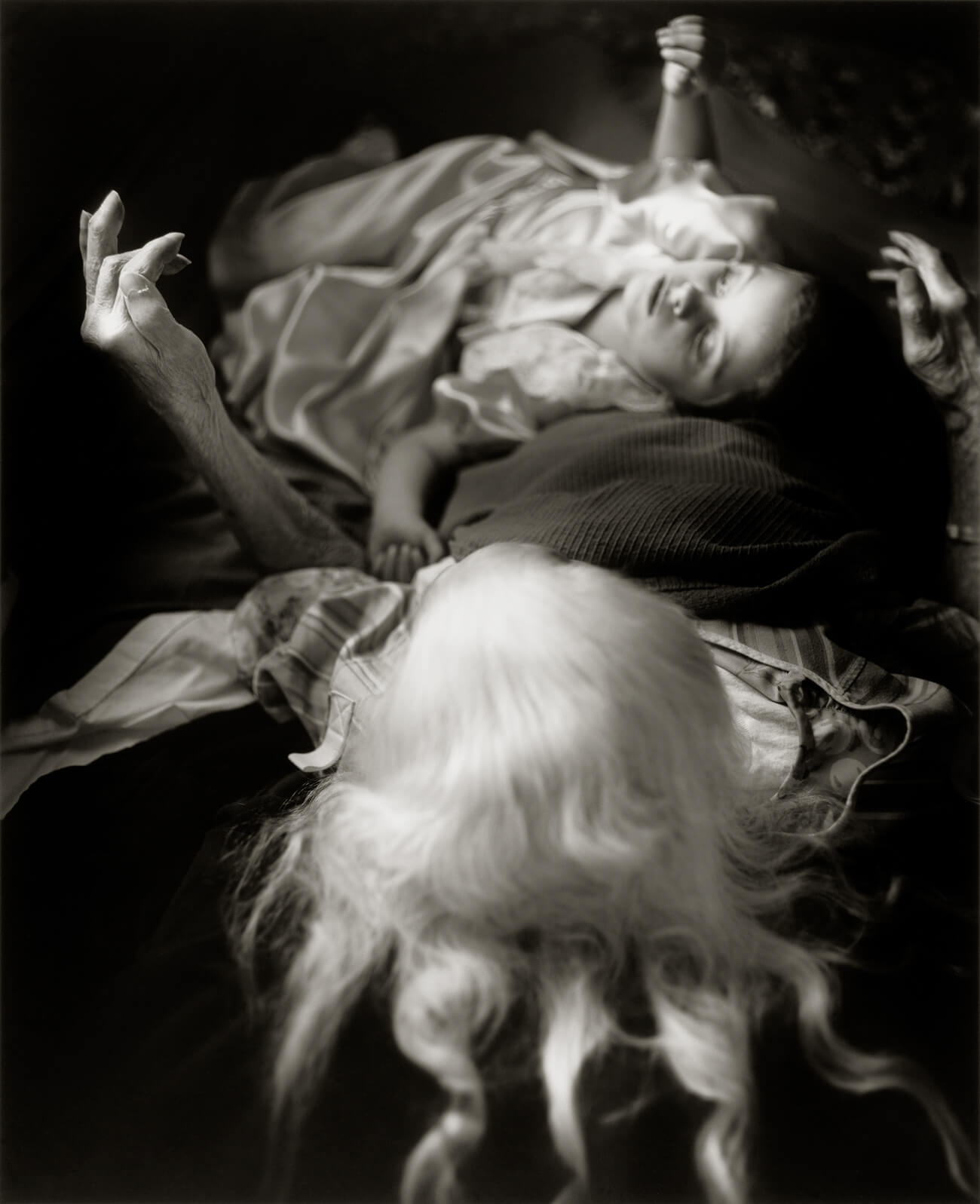 An elderly woman with long white hair lies prone under a blanket, with a young girl lying across her legs.