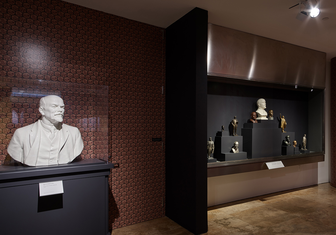 Gallery interior showing display cases with busts of Vladimir Lenin in various sizes, colors, and materials