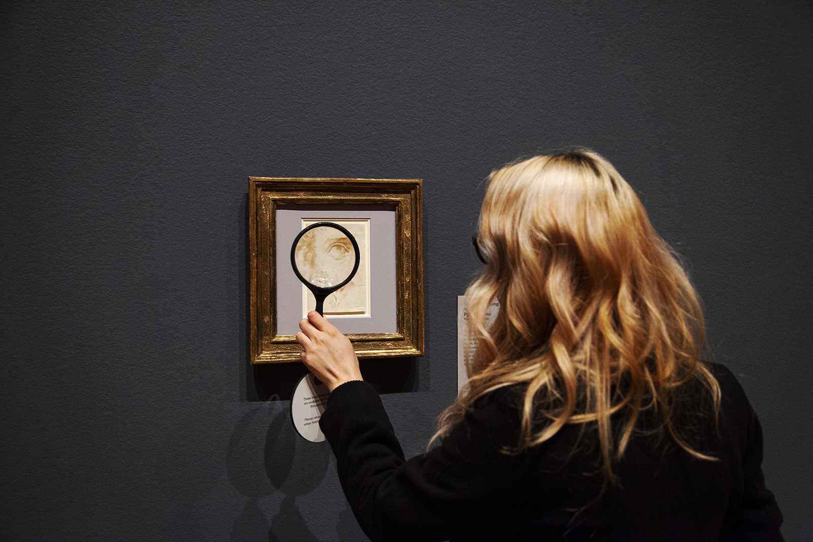 Blond woman holds a magnifying glass to a framed sketch, enlarging an eye.