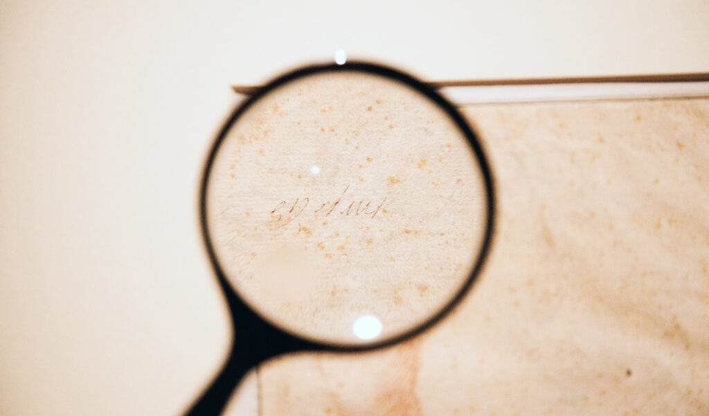 A magnifying glass is held up to faint words on the corner of a sketch.