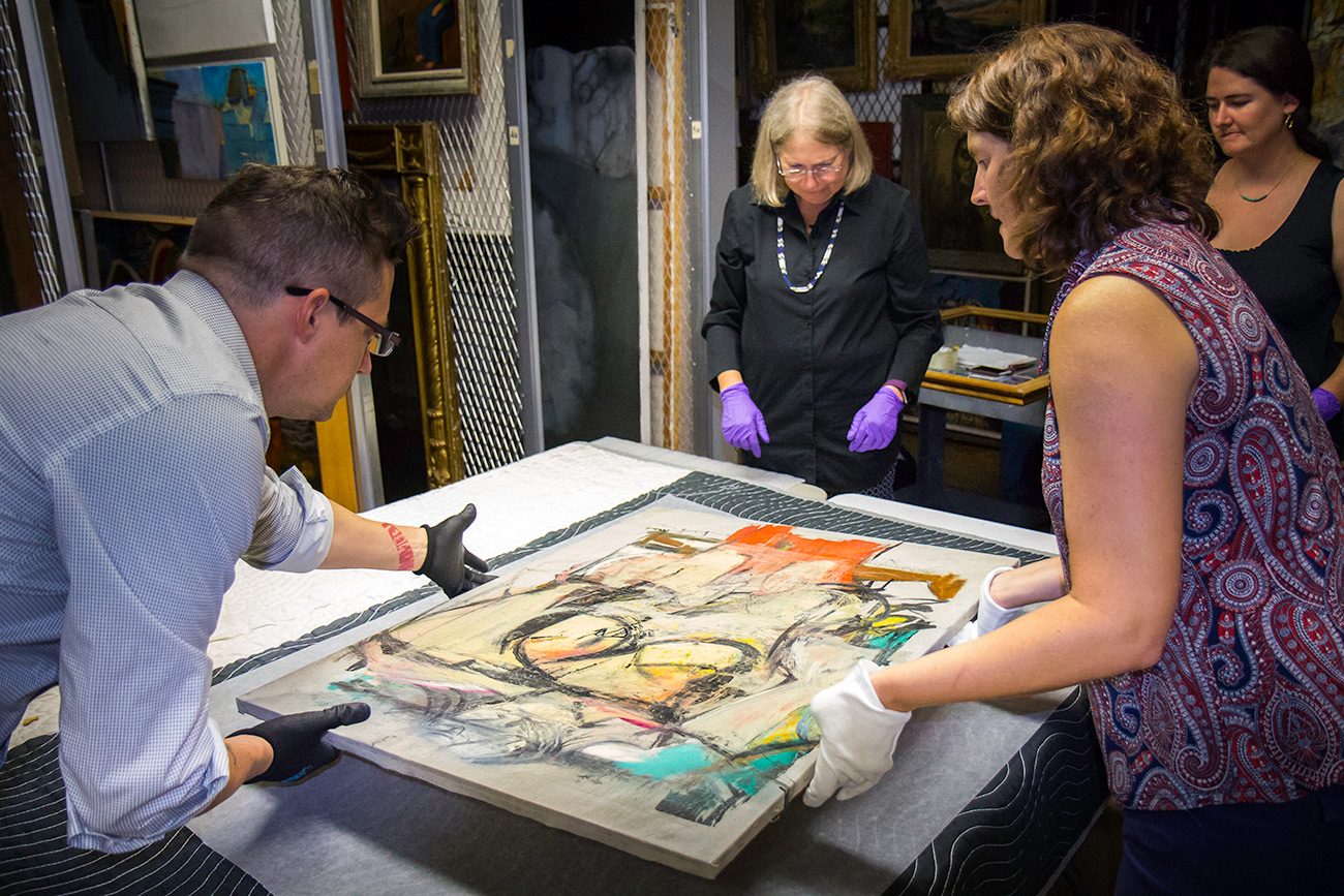 Three conservators examine an abstract painting featuring colors of soft gold, turquoise, and coral. Willem de Kooning, Woman-Ochre, 1955. Oil on canvas, 30 x 40 in. Copyright 2019 The Willem de Kooning Foundation / Artists Rights Society (ARS), New York