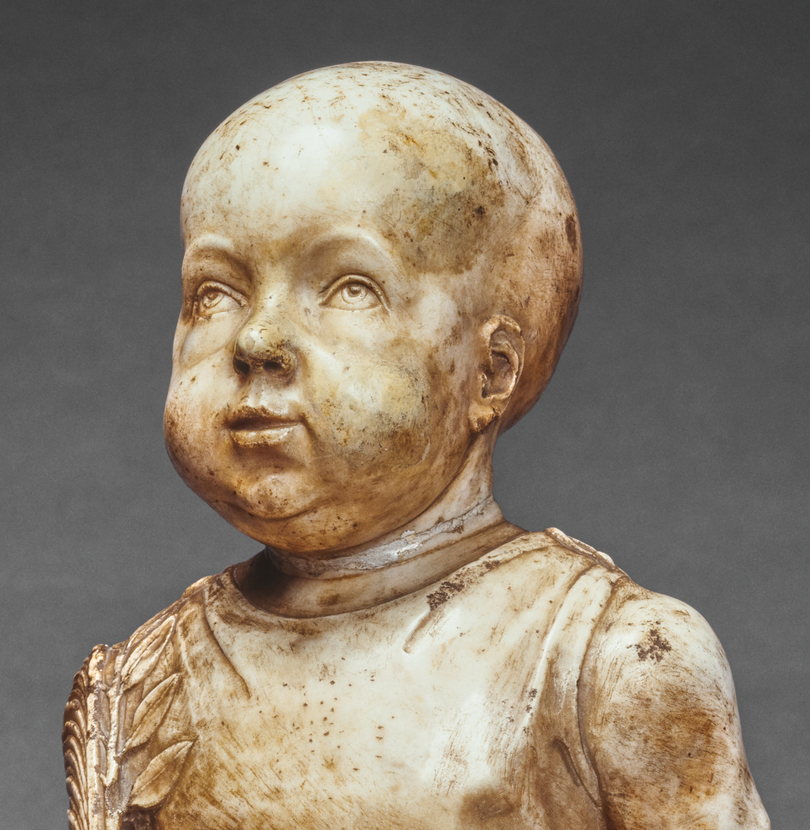 Dirty bust of a bald baby wearing a toga with laurel leaves along the left side.