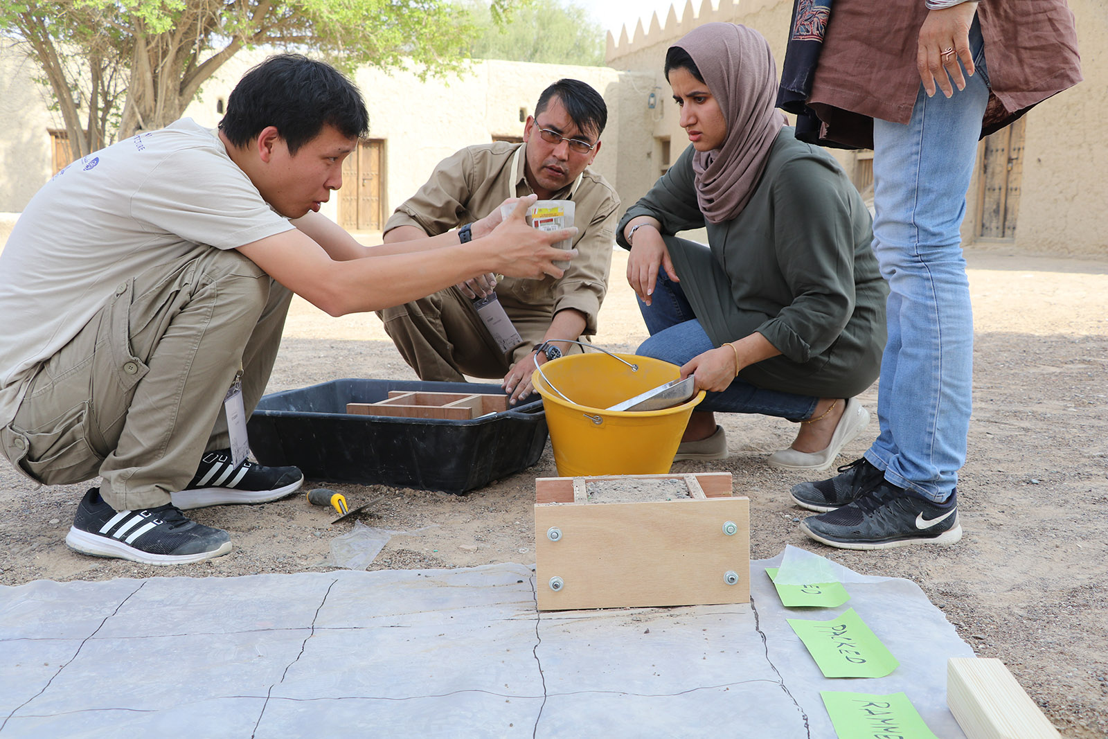 In a dirt courtyard, a man holds a container in which he, another man, and Eithar, a young woman wearing a mauve headscarf, a green smock, and blue jeans, look at a container holding a substance for an exercise.