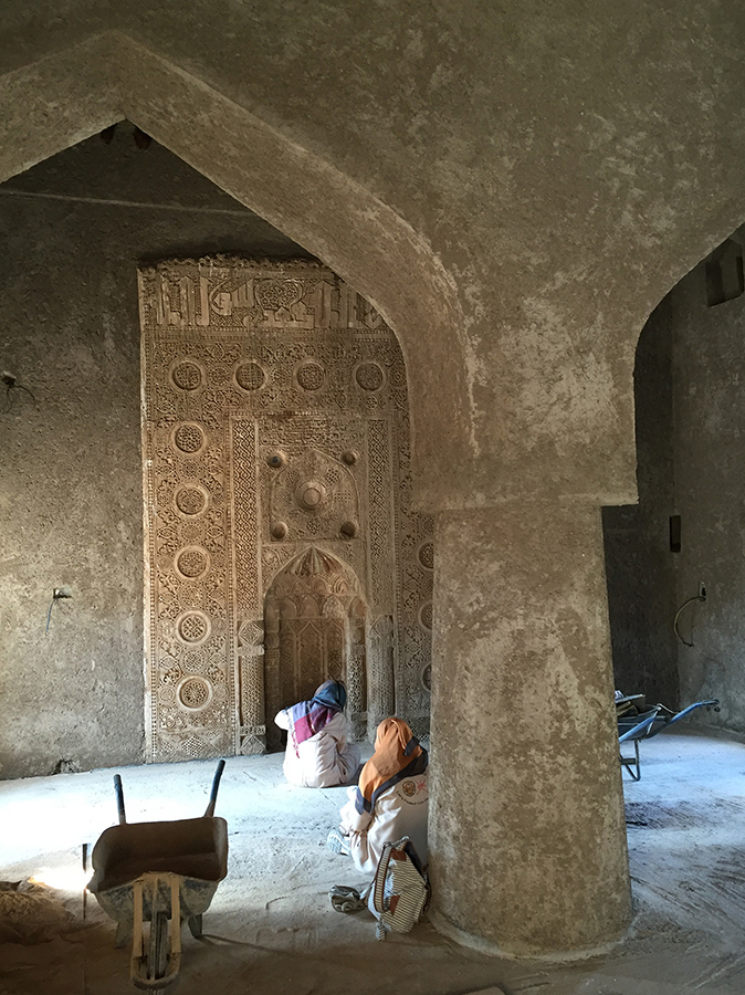 Two women sit cross-legged on the floor of an old mosque, looking towards an intricately decorated wall.