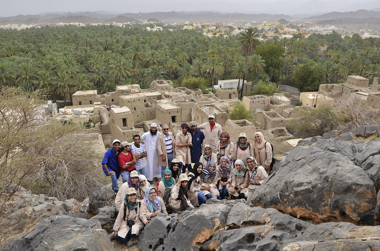 A group of smiling men and women in hats, headscarves, and beige coats stand and sit above the remains of a old settlement and a large expanse of palm trees.