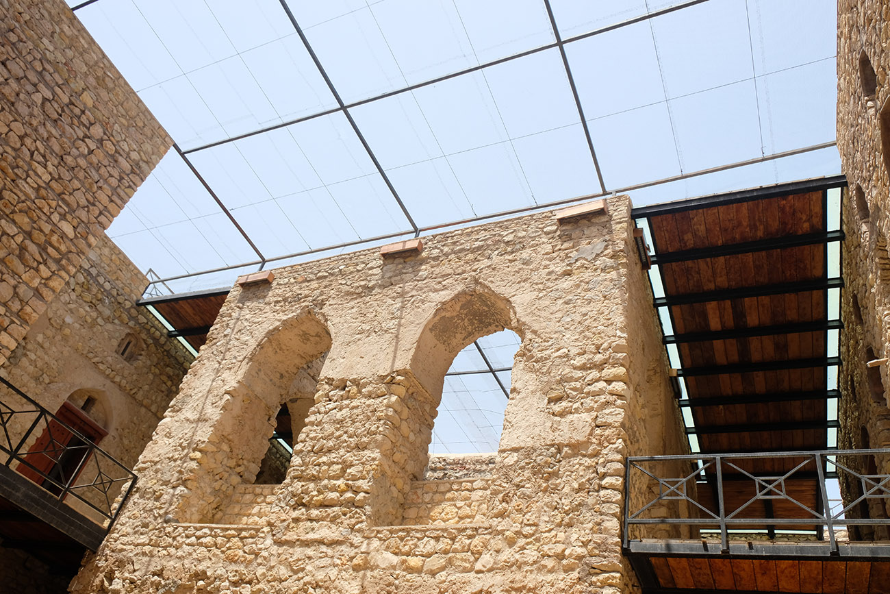 An upwards perspective on sand-colored walls with exposed stone, inset with lancet windows.