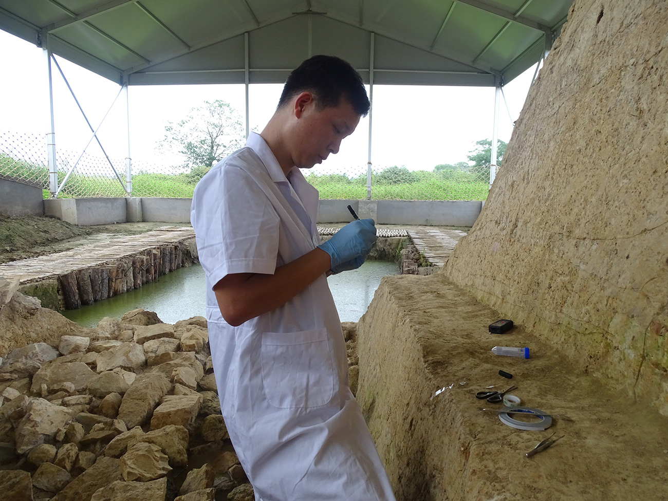 Cui Biao, a young Chinese man, wears white coveralls and blue gloves as he collects samples at an archaeological ruin.