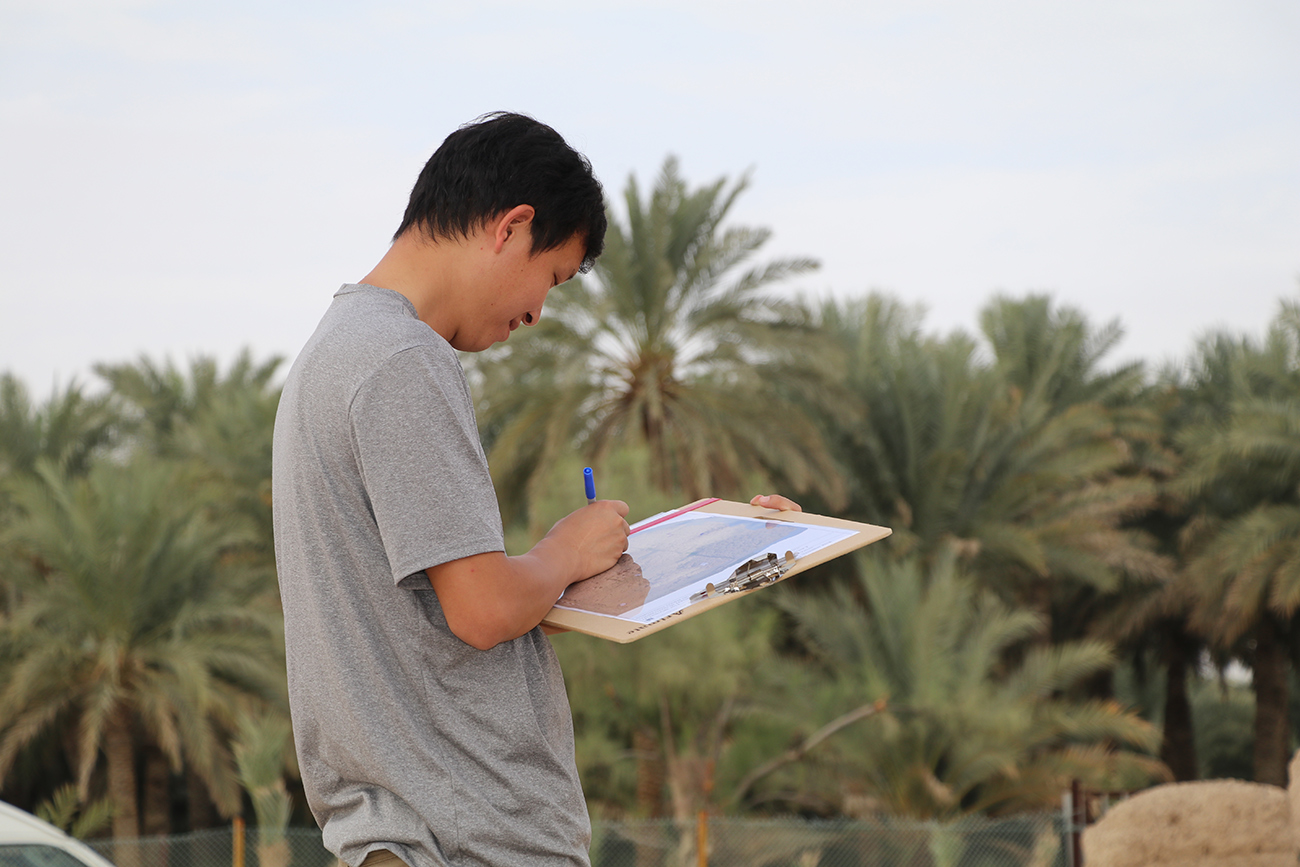 Against a background of palm trees, Cui Biao makes notes on a map clipped to a clipboard.