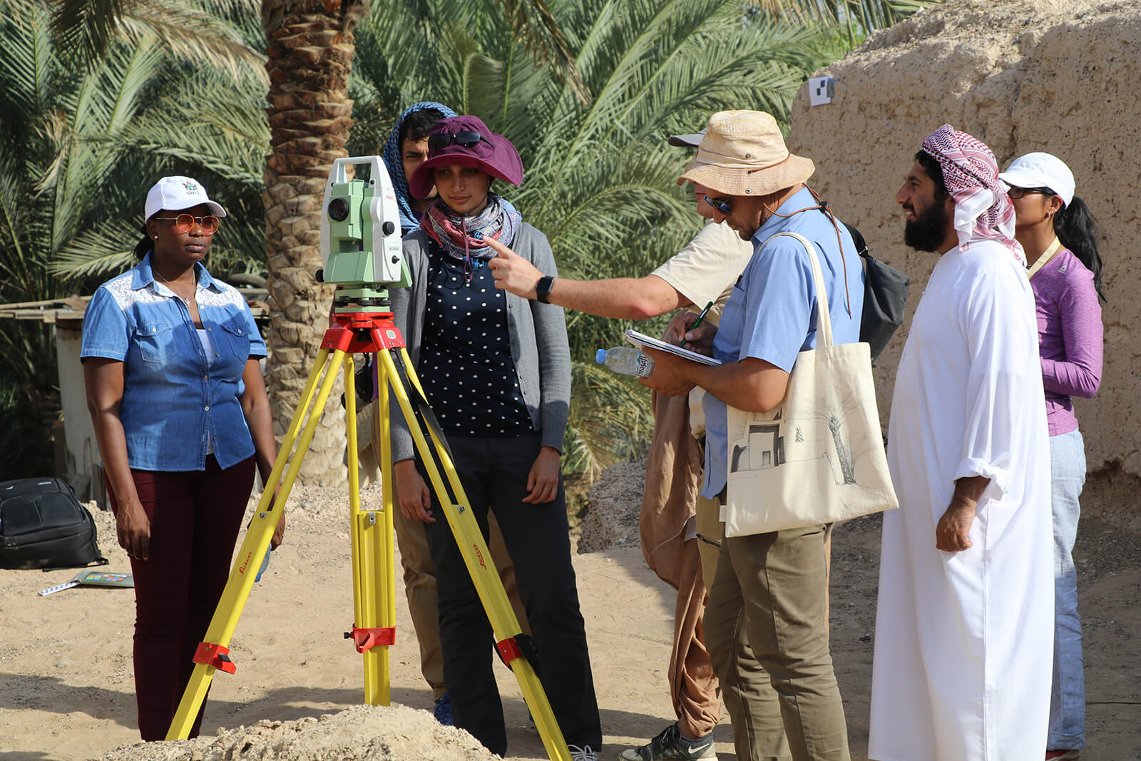 Gayathri Hegde, a young Indian woman, and other course participants stand near a theodolite mounted on a tripod.