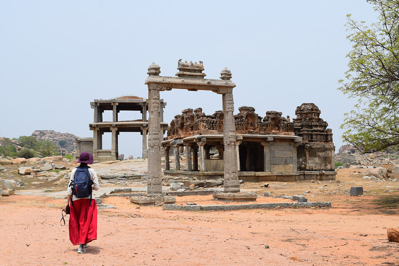 Gayathri, wearing a purple hat and carrying a blue backpack, walks towards the ruins of several old buildings in a dry landscape.