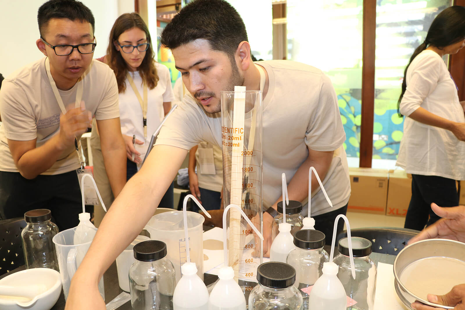 Sajjad Sharifi, a young man wearing a beige t-shirt, reaches across a table crowded with beakers and jars, with other course participants visible in the background.