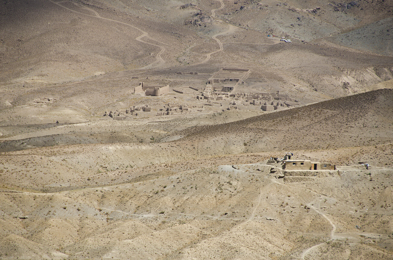 Sand-colored ruins of several structures occupy an equally sand-colored landscape dotted with brush.